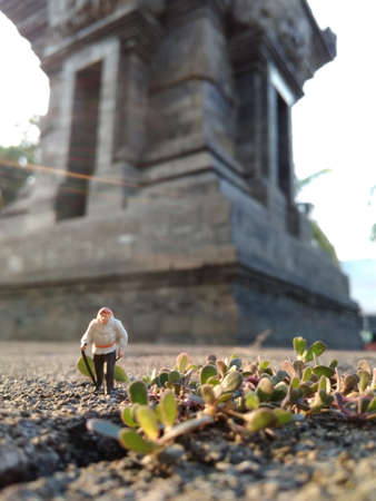Mini Figure adventurer Walking at stone road passing by big Temple