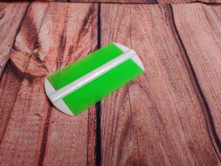 serit, cheap white and green plastic comb to grab bug and it's eggs from human hair at wooden table Stock Photo