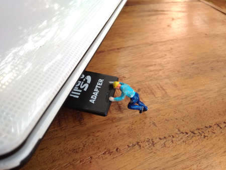 miniature figure engineer toy inserting memory card into slot at white notebook