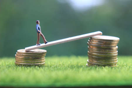 miniature figure young bussinesman keep trying to get higher income walking at stack of coin at fresh green grass in the morning Imagens