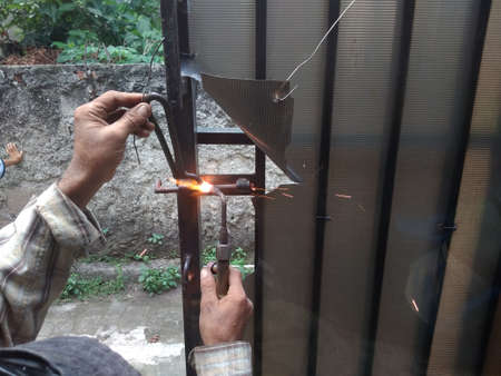 Old Man Welding a Corrosive Black Iron Handle of Gate Imagens