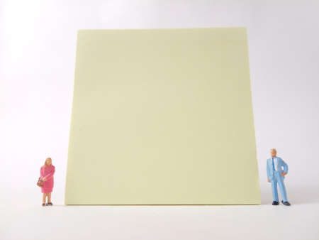 Conceptual Businessman and Woman doing Presentation, near at big blank Yellow paper, at white backround