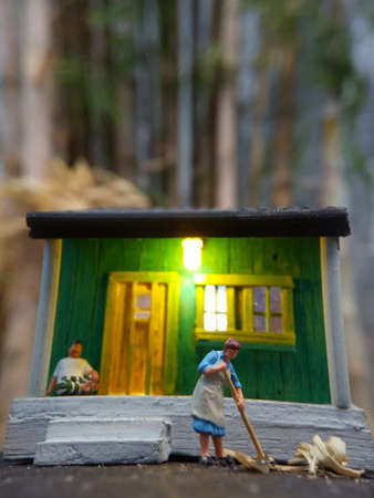 Mini figure toy Indonesian woman cleaning the terrace and old man using sarung, kopiah and white shirt, sit at his house, beyond bamboo forest with copy or negative space for text placement area