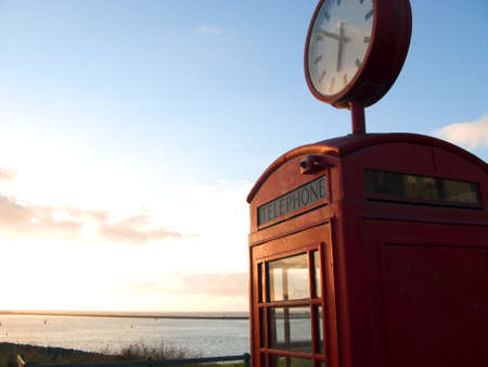 cell phone booth: Red telephone box with view at sea