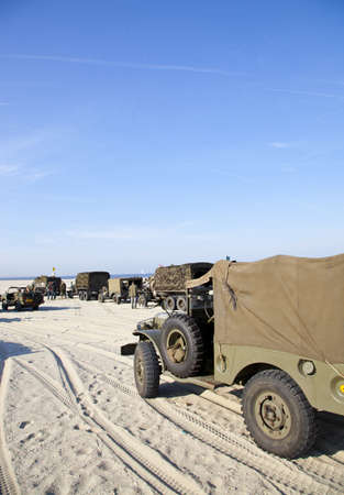 simulate: IJMUIDEN, THE NETHERLANDS-MAY 5: Army trucks riding on beach on May 5,2011 in IJmuiden The Netherlands. Army trucks riding on beach to celebrate liberation of Second World War and simulate arrival of allies Editorial