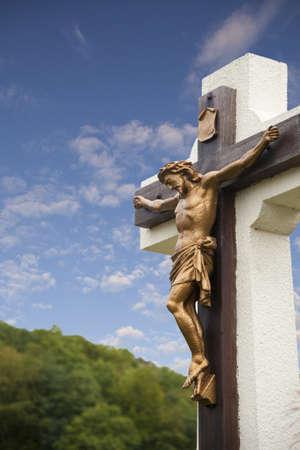 Standbeeld van Jezus aan kruis met blauwe hemel Stockfoto