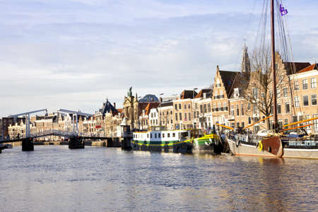 View at Dutch canal with old bridge, boats and churches at Haarlem, The Netherlands