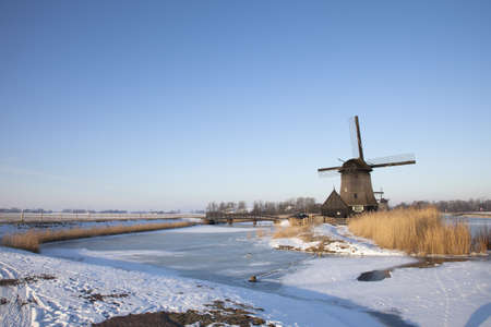 Windmill in winter time with snow and blue sky Stock Photo