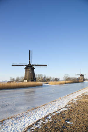 typically dutch: Two windmills in winter time with snow, ice and blue sky Stock Photo