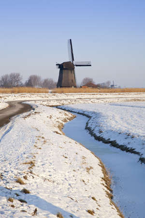 typically dutch: Windmill in winter time with snow, ice and blue sky Stock Photo