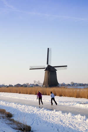 Windmill in winter time with snow, ice and blue sky Stock Photo