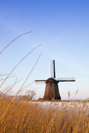 Windmill in winter time with snow and blue sky photo