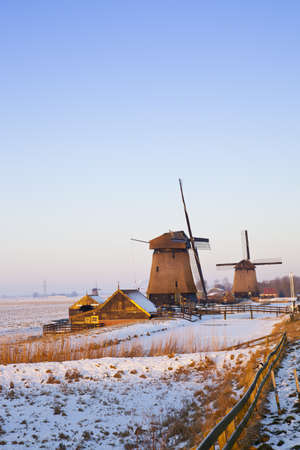 typically dutch: Windmill in winter time with snow and blue sky Stock Photo