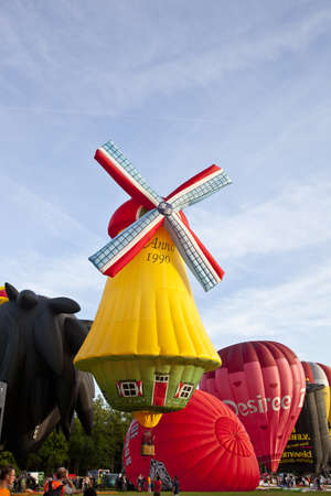 BARNEVELD, THE NETHERLANDS - 17 AUGUST 2012: Colorful windmill and red air balloons taking off at international balloon festival Ballonfiesta in Barneveld on August 17 in Barneveld, The Netherlands