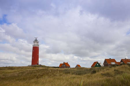 Red lighthouse and houses on island Texel, The Netherlands photo