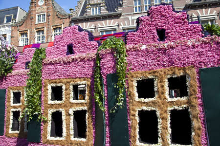 HAARLEM, THE NETHERLANDS - APRIL 21 2013: Dutch houses with flowers at flower parade on April 21 2013 in Haarlem, The Netherlands. The annual flower parade is a unique event with one million visitors.