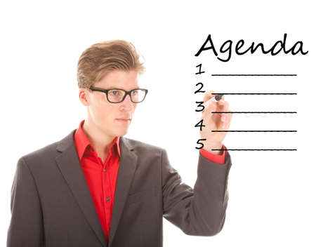 Young man with pen writing an agenda isolated on white background photo