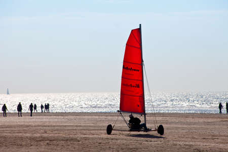 ijmuiden: IJMUIDEN, THE NETHERLANDS -MARCH 20TH 2011: Beach sailing cart (Blokart) with red sail on the beach in IJmuiden on March 20th 2011