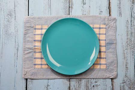 plato de comida: Plato vacío sobre la luz de fondo de madera azul Foto de archivo