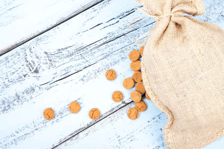 zwarte: Dutch candy pepernoot with jute bag on white blue wooden background Stock Photo