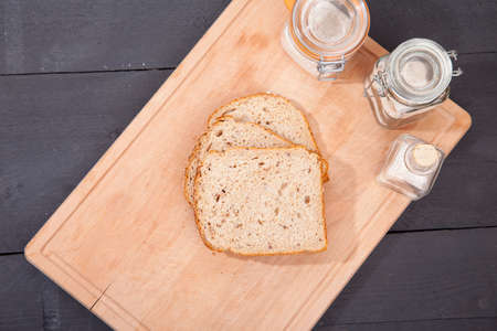 allergic ingredients: Gluten free bread on plate with spelled flower on black wooden background Stock Photo