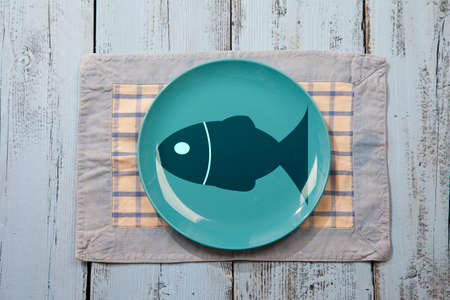 empty plate: Empty plate with fish illustration on light blue wooden background
