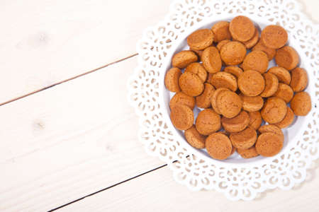 sinterklaasfeest: Traditional Dutch candy pepernoot on white plate on white wooden background Stock Photo