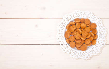 strooigoed: Traditional Dutch candy pepernoot on white plate on white wooden background Stock Photo