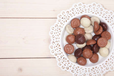 strooigoed: Traditional Dutch chocolate candy pepernoot on white plate on white wooden background Stock Photo