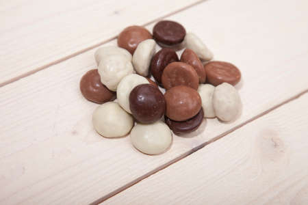 strooigoed: Pile of Dutch candy chocolate pepernoten on white wooden background