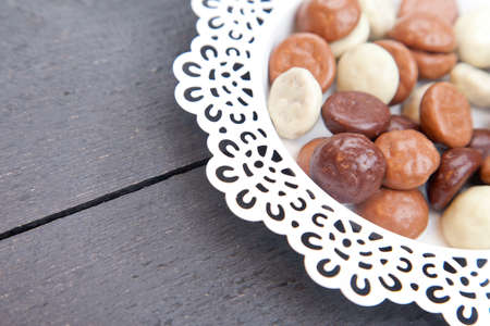 strooigoed: Dutch candy chocolate pepernoten on white plate on black wooden background Stock Photo