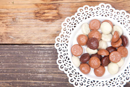 strooigoed: Dutch candy chocolate pepernoten on white plate on brown wooden background