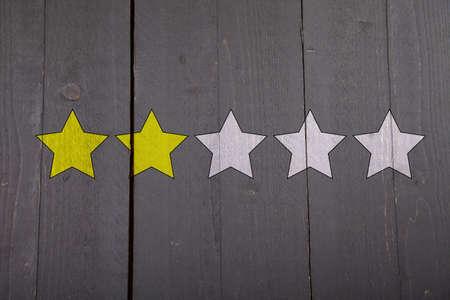 ranking: Two yellow ranking stars on black wooden background Stock Photo