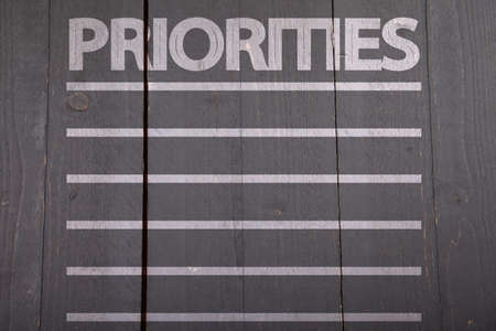priorities: Priorities list on black wooden background Stock Photo