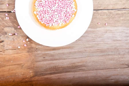 dutch girl: Traditional Dutch birth celebration biscuit with pink muisjes on wooden background Stock Photo
