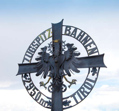 ZUGSPITZE, AUSTRIA - August 15, 2016: Famous symbol on top of huge mountain Zugspitze in Austria Editorial