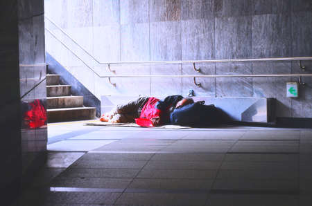 social outcast: Vintage photo of homeless man rsleep in subway under the sunlight Editorial