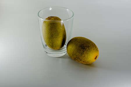 actinidia deliciosa: water glass and two fresh kiwi fruit actinidia deliciosa on dark background