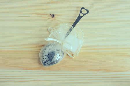 tea filter: Spoon metal for filter tea on wooden background: Vintage Stock Photo