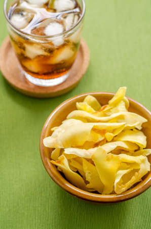 fried snack: Cola and durian chips fried snack fruit in brown blow on green background