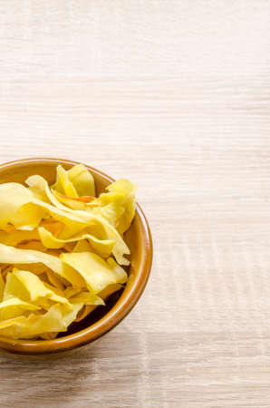 fried snack: Durian chips fried snack fruit in brown blow on wooden background Stock Photo