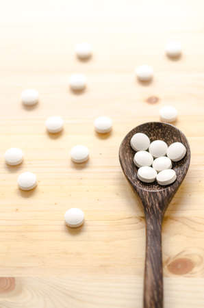medicine tablets and wooden spoon on wood background Stock Photo