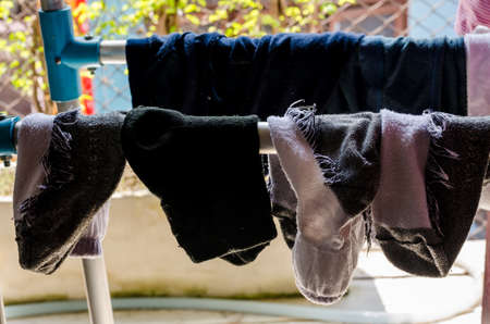 muddy clothes: Used socks hang on hanger in house