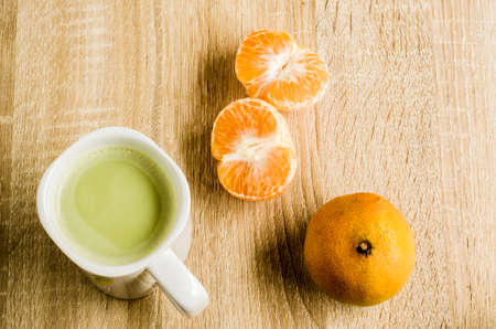 Hot green tea latte and fresh of Orange on wooden table background