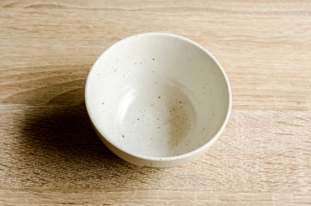 precarious: white bowl isolated on wooden background