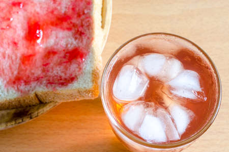 strawberry jam sandwich: Ice berry tea and Bread with homemade jam on wooden table