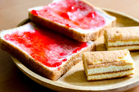 strawberry jam sandwich: Bread with homemade jam on wooden table Stock Photo
