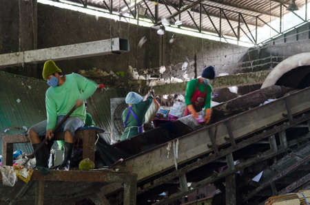 pile reuse engine: TRAT PROVINCE, THAILAND-JULY 15 2016, Picture blur of Workers in separate line collect the plastic and metallic waste from household in waste disposal factory. Editorial