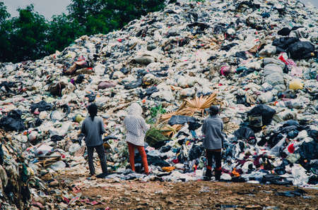 pile reuse engine: SAKAEO PROVINCE, THAILAND-JULY 12 2016, Three worker in Waste dump site, municipal waste from Sakaeo province, Thailand