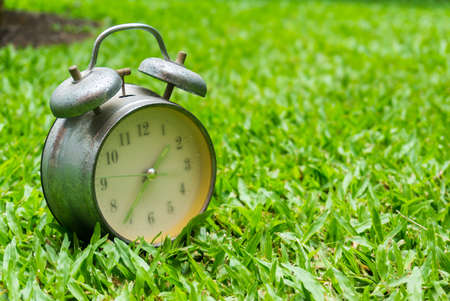 An old clock on green glass in the morning Stock Photo